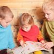 Stock Photo: Children read book on sofa in the wooden room