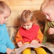 Stock Photo: Children read book on sofa in the wooden room 2