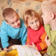 Stock Photo: Children read book on sofa in the wooden room 3
