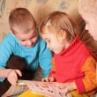Stock Photo: Children read book on sofa in the wooden room 4