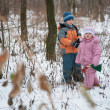 Brother with sister in forest in winter - Stock Photo