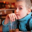 Stock Photo: Soiled boy drinks juice from glass through straw