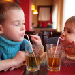 Little boy and girl drink juice from glasses through straws — Stock Photo #7439600