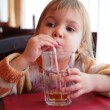 Little girl drinks juice from glass through straw — Stock Photo