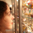 Young woman looks on showcase with souvenirs — Stock Photo