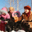 Two mothers with children and dog on street in winter - Stock Photo