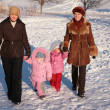 Two mothers with children on walk in winter - Stock Photo