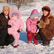 Two mothers with children outdoor in winter - Stock Photo
