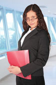 Beautiful brown-haired woman with red folder in the hall of biss — Stock Photo