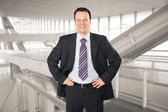 Smiling businessman in glass hall — Stock Photo