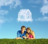 Smiling couple on grass and dream cloud house collage — Stock Photo