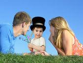 ребенок в шляпе с матерью и отцом на траве, коллаж — Стоковое фото