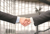 Shaking hands with wrists in hall of business center — Stock Photo