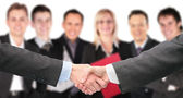 Shaking hands with wrists and six business group out of focus co — Stock Photo