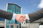 Shaking hands with wrists near blue building — Stock Photo