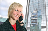 Blond woman with phone near Modern glass building — Stock Photo