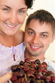 Smiling man and young woman eat cherries — Stockfoto