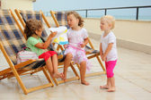 Three little girls in lounge on veranda, considering drawing — Foto Stock
