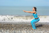 Woman is making exercise on sea coast — Stock Photo