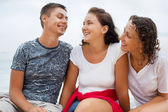 Smiling man and two young beautiful women sitting on beach, Loo — Stock Photo