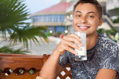 Young smiling man sitting in an arbour on resort, drinking kefir — Stock Photo