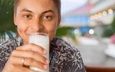Jovem sorridente bebendo kefir sentado em uma haste sobre resort — Foto Stock