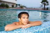 Teenager boy relaxing near ledge in pool open-air, looking at ca — Stock Photo