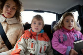 Mother with son and daughter sit in car — Stok fotoğraf
