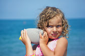 Pretty little girl holds in hands pebble on seacoast in afternoo — Stock Photo