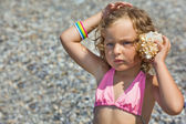 Pretty little girl has leant seashell bowl to an ear on seacoast — Stock Photo