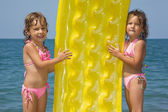 Two little girls standing on beach, having control over an infla — Stock Photo