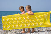 Two pretty little girls bearing in hands inflatable mattress on — Stock Photo