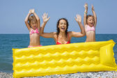 Young woman and two little girls standing behind an inflatable m — Stock Photo