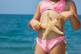 Body of little girl with starfish on beach — Stock Photo