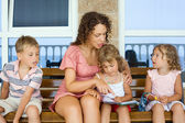 Young beautiful woman reads book to two little girls and boy on — Stockfoto