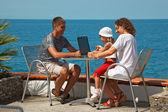 Famille reposant sur la mer avec ordinateur portable — Photo