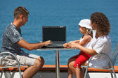 Family resting on sea with laptop — Stok fotoğraf