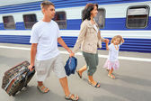 Happy family with little girl going on railway station — Stock Photo
