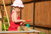 The girl plays to a sandbox. Horizontal format. — Stock Photo