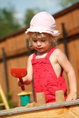 The girl plays to a sandbox. Vertical format. — Stock Photo