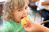 Pretty little girl eats hamburger from mothers's hand — Stock Photo