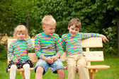 Drei Kinder auf einer Parkbank identische Kleidung — Stockfoto