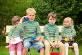 Two boys and two girls on a bench in park. In identical stripe c — Stock Photo