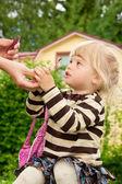 Mamma ger till en dotter läppstift utomhus — Stockfoto