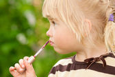 The little girl paints lips — Stock Photo