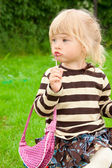 The little girl paints lips in park — Stock Photo