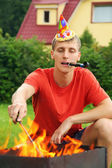Young man with calumet near brazier on picnic, happy birthday pa — Stock Photo