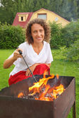 Young woman near brazier on picnic — Stock Photo