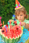 Dziewczynka w wpr zjada owoce w ogrodzie, szczęśliwy urodziny — Zdjęcie stockowe