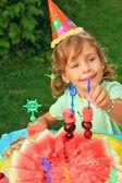 Little girl in cap eats fruit in garden,happy birthday — Stock Photo